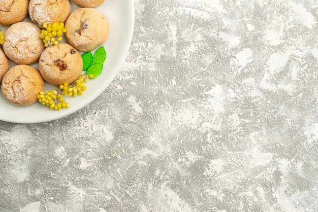 Vista superior deliciosos biscoitos de açúcar dentro do prato no fundo branco biscoito de açúcar biscoito doce bolo chá
