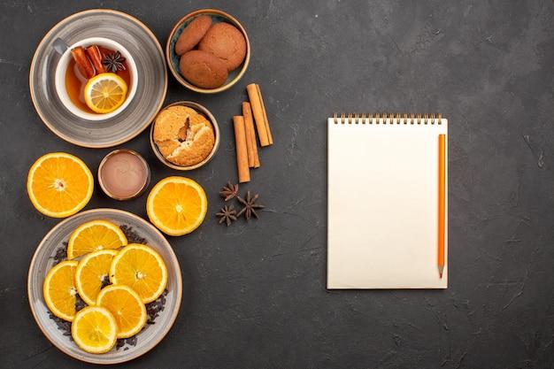 Vista superior deliciosos biscoitos de areia com laranjas frescas cortadas e uma xícara de chá na mesa escura.