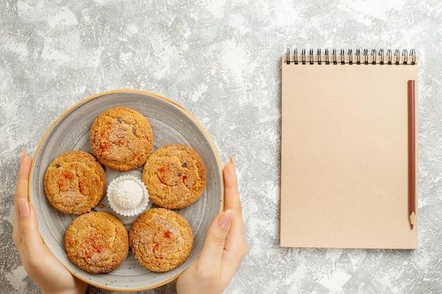 Vista superior deliciosos biscoitos de areia dentro do prato em fundo branco claro