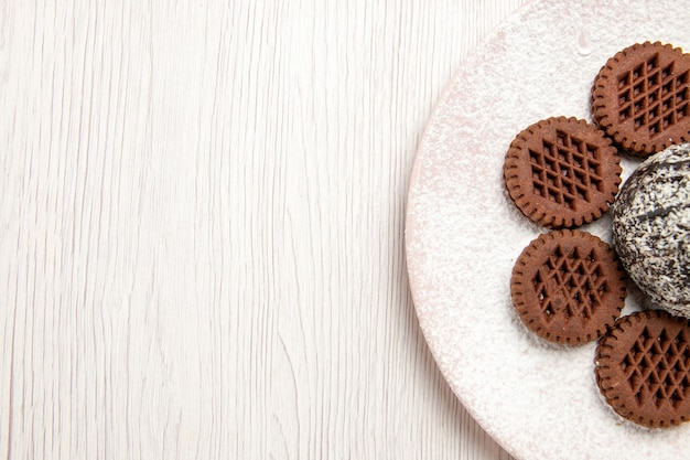 Vista superior deliciosos biscoitos de chocolate com bolinho de cacau em branco
