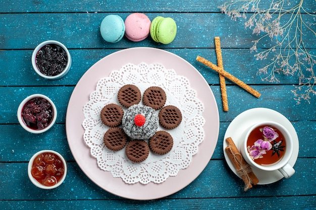 Vista superior deliciosos biscoitos de chocolate com geleia e xícara de chá na mesa rústica azul.