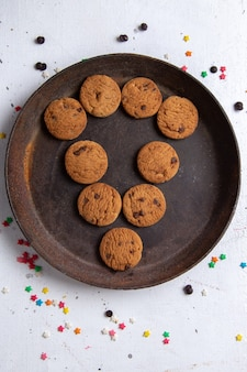 Vista superior deliciosos biscoitos de chocolate dentro de um prato redondo marrom e forrado no fundo branco biscoito biscoito açúcar doce chá