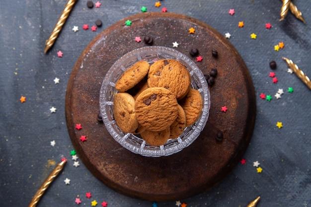 Vista superior deliciosos biscoitos de chocolate dentro de uma tigela transparente com velas no fundo cinza escuro biscoito biscoito açúcar chá doce