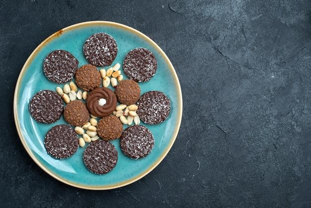 Vista superior deliciosos biscoitos de chocolate redondos formados dentro do prato sobre fundo cinza escuro biscoito bolo de açúcar torta doce chá biscoitos