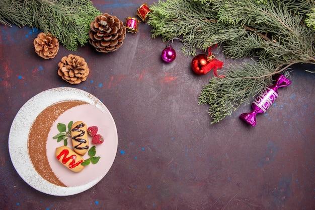 Vista superior deliciosos biscoitos doces com brinquedos de natal e árvore no fundo escuro.