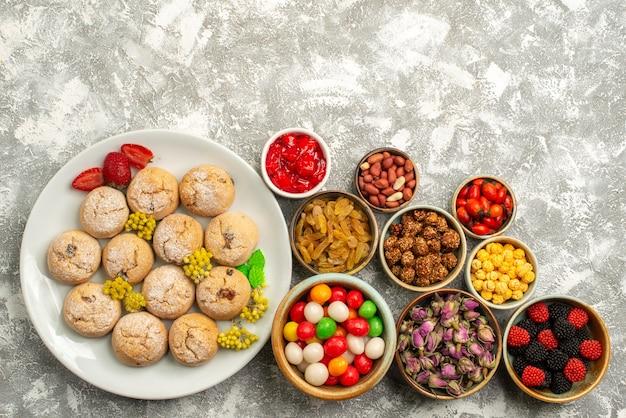 Vista superior deliciosos biscoitos doces com doces e nozes no chão branco doce biscoito biscoito doce chá açúcar
