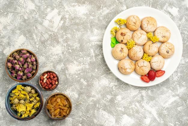 Vista superior deliciosos biscoitos doces com nozes e passas no fundo branco.