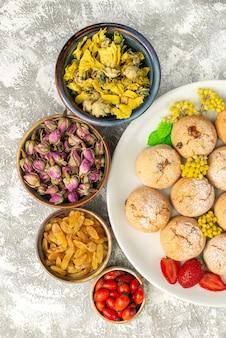Vista superior deliciosos biscoitos doces com passas e nozes na superfície branca doce biscoito biscoito doce chá açúcar