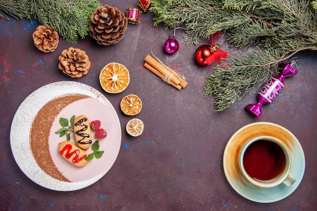 Vista superior deliciosos biscoitos doces com uma xícara de chá e árvore de natal em fundo escuro.