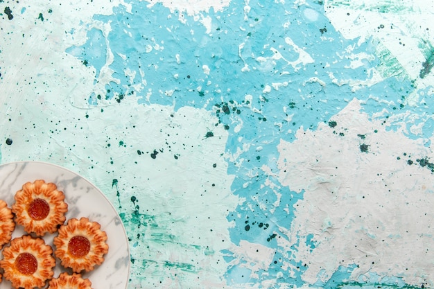 Vista superior deliciosos biscoitos redondos formados com geleia dentro do prato no fundo azul claro biscoito açúcar doce biscoito bolo