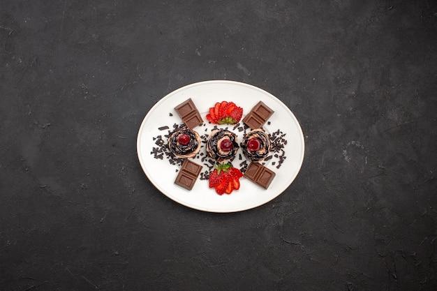 Vista superior deliciosos bolinhos com barras de chocolate e morangos no fundo escuro torta de bolo de cacau chá doce