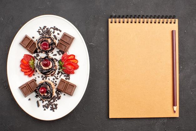 Vista superior deliciosos bolinhos com barras de chocolate e morangos no fundo escuro torta de bolo de cacau doce