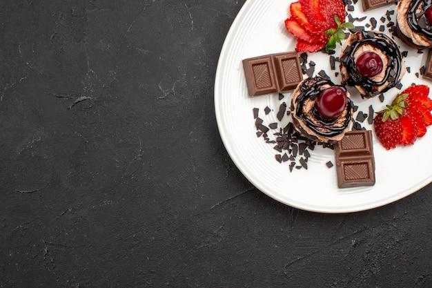 Vista superior deliciosos bolinhos com barras de chocolate e morangos no fundo escuro torta de chocolate bolo de cacau chá doce