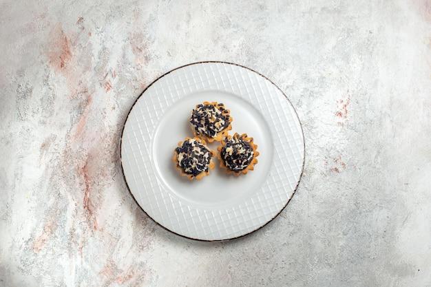 Vista superior deliciosos bolinhos com gotas de chocolate dentro do prato no fundo branco bolo biscoito doce creme chá sobremesa