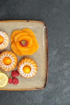 Vista superior deliciosos bolinhos com rodelas de limão e tangerinas em um fundo escuro, biscoito de frutas, torta doce de chá