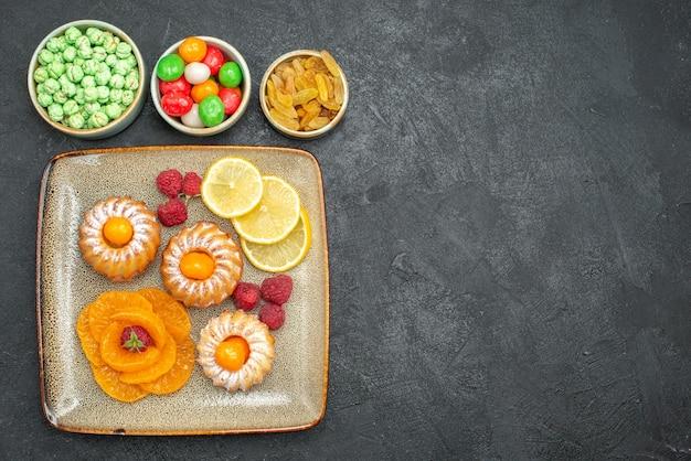 Vista superior deliciosos bolinhos com rodelas de limão, tangerinas e doces em fundo escuro, chá, fruta, biscoito, torta de biscoito doce