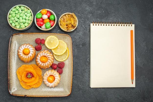 Vista superior deliciosos bolinhos com rodelas de limão, tangerinas e doces em fundo escuro, chá, fruta, biscoito, torta