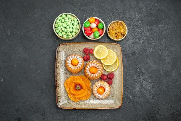 Vista superior deliciosos bolinhos com rodelas de limão, tangerinas e doces em fundo escuro, chá, frutas, biscoito, torta de biscoito doce