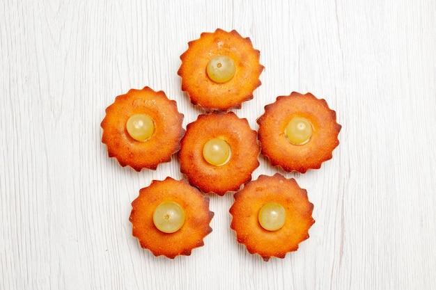 Vista superior deliciosos bolinhos doces perfeitos para chá forrado em mesa branca torta de bolo doce sobremesa biscoito de chá