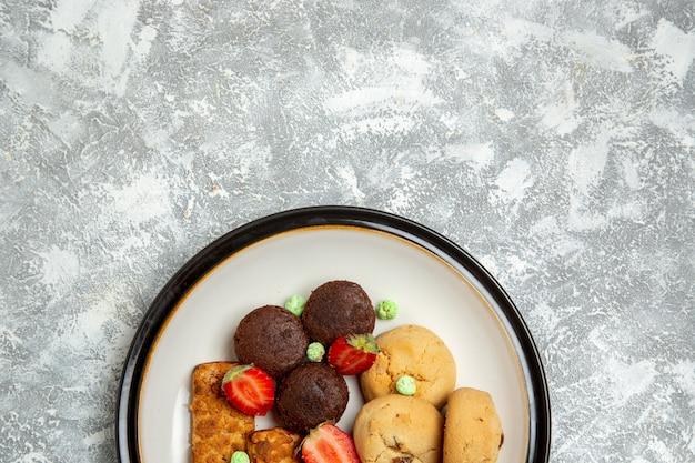 Vista superior deliciosos bolos com biscoitos e morangos na mesa branca biscoito açúcar bolo torta doce chá