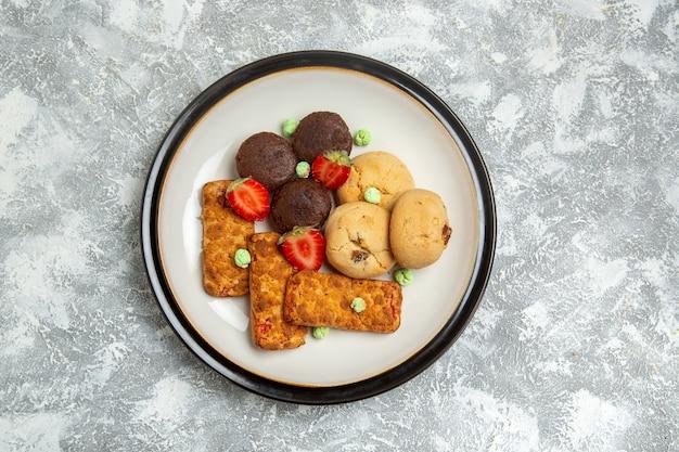 Vista superior deliciosos bolos com biscoitos e morangos na superfície branca biscoito bolo de açúcar torta doce chá biscoito