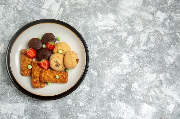 Vista superior deliciosos bolos com biscoitos e morangos no fundo branco biscoito bolo de açúcar torta doce chá