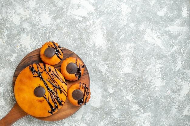 Vista superior deliciosos bolos com chocolate e cobertura na superfície branca torta sobremesa bolo cacau chá doce