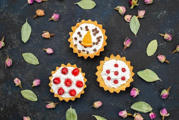 Vista superior deliciosos bolos com creme com frutas no topo isolados na superfície escura açúcar doce fruta