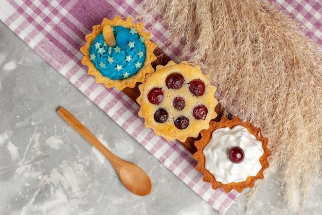 Vista superior deliciosos bolos com creme e frutas na superfície clara bolo doce creme asse frutas chá