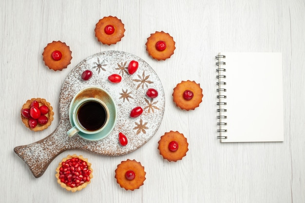Vista superior deliciosos bolos com frutas e xícara de chá na mesa branca
