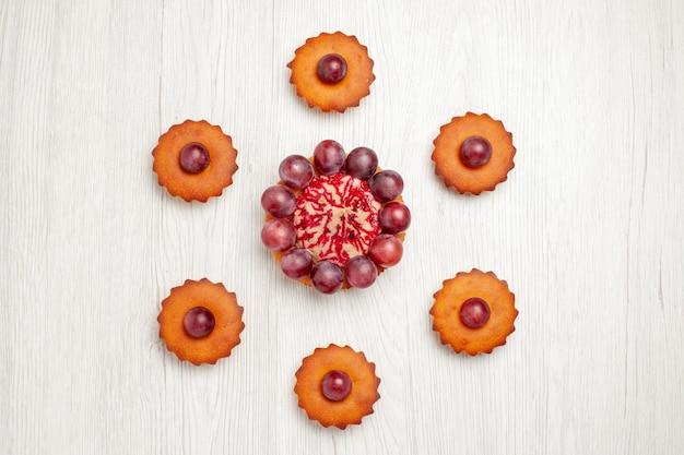 Vista superior deliciosos bolos com uvas na mesa branca biscoito de torta de sobremesa
