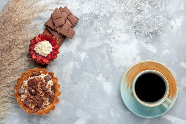 Vista superior deliciosos bolos cremosos com barras de chocolate e chá na mesa branca bolo biscoito doce açúcar