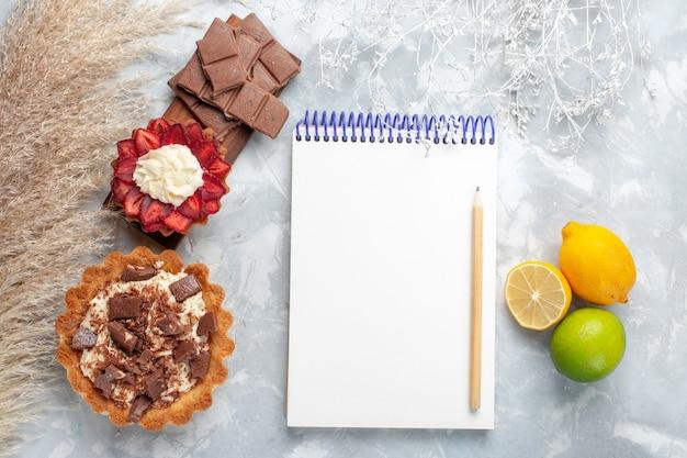 Vista superior deliciosos bolos cremosos com barras de chocolate e limão na mesa branca bolo biscoito doce açúcar
