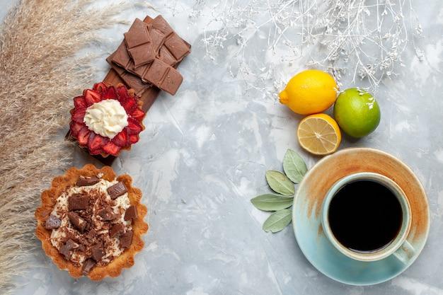 Vista superior deliciosos bolos cremosos com barras de chocolate, limão e chá na mesa branca bolo biscoito doce açúcar