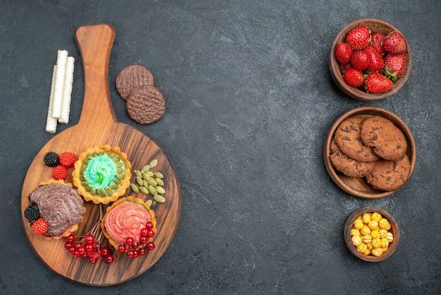Vista superior deliciosos bolos cremosos com biscoitos na mesa escura biscoito doce sobremesa