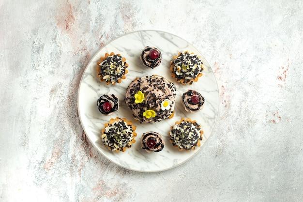 Vista superior deliciosos bolos cremosos com caroços de chocolate na superfície branca bolo biscoito biscoito chá doce creme