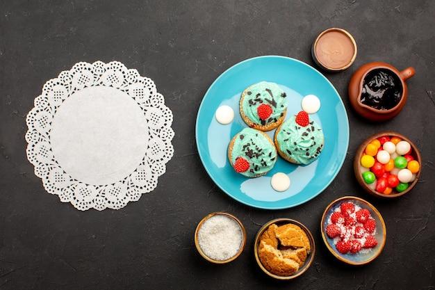 Vista superior deliciosos bolos cremosos com doces em fundo escuro.