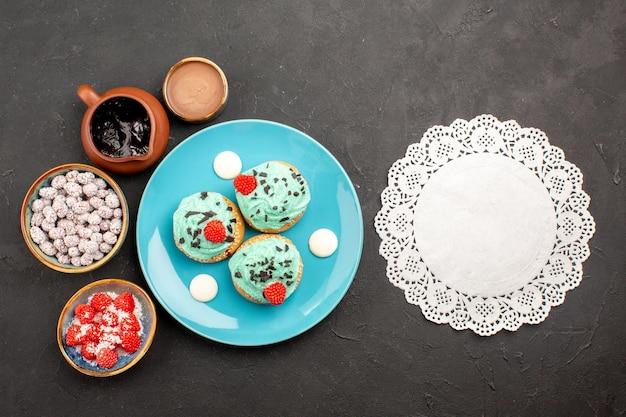 Vista superior deliciosos bolos cremosos com doces em fundo escuro