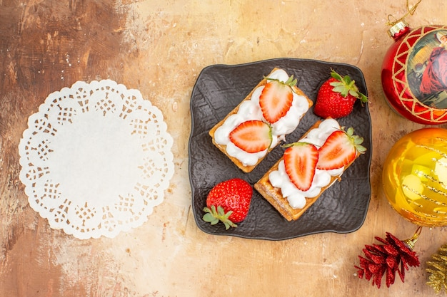 Vista superior deliciosos bolos cremosos com frutas e brinquedos para árvores de férias em fundo claro