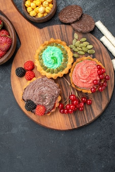 Vista superior deliciosos bolos cremosos com frutas em biscoitos doces de mesa escuros