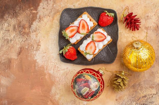 Vista superior deliciosos bolos cremosos com frutas em fundo claro