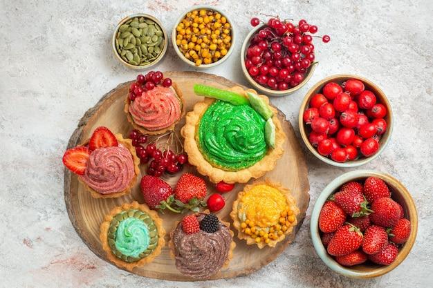 Vista superior deliciosos bolos cremosos com frutas frescas em uma torta de mesa branca sobremesa doce