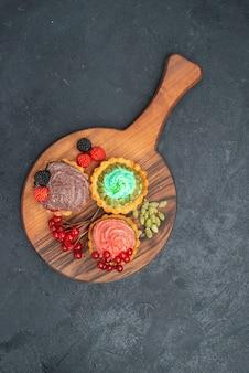 Vista superior deliciosos bolos cremosos com frutas vermelhas em um biscoito de mesa escuro