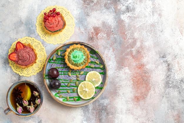 Vista superior deliciosos bolos cremosos com xícara de chá em biscoito doce doce de fundo claro
