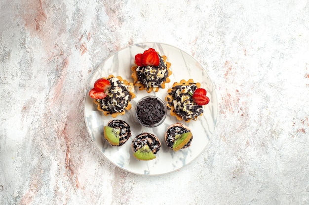 Vista superior deliciosos bolos cremosos sobremesas para chá com frutas e gotas de chocolate em uma superfície branca bolo de frutas torta de biscoito com creme chá
