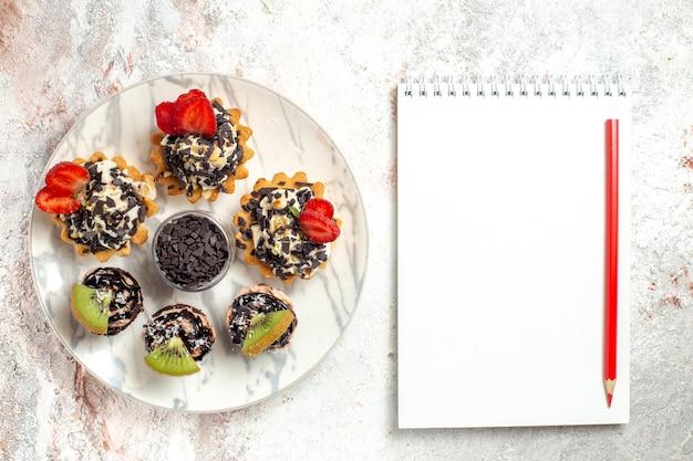 Vista superior deliciosos bolos cremosos sobremesas para chá com gotas de chocolate na superfície branca bolo de frutas torta de biscoito com creme chá