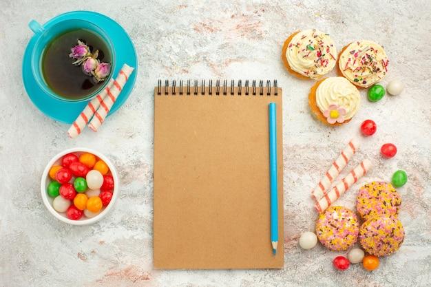 Vista superior deliciosos bolos de biscoito com doces coloridos e uma xícara de chá na superfície branca do bolo de biscoito da cor da torta de biscoito