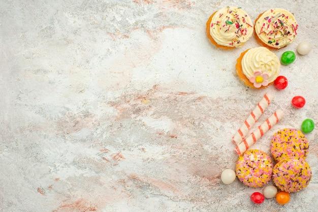 Vista superior deliciosos bolos de biscoito com doces coloridos na superfície branca do bolo de biscoito da cor da torta