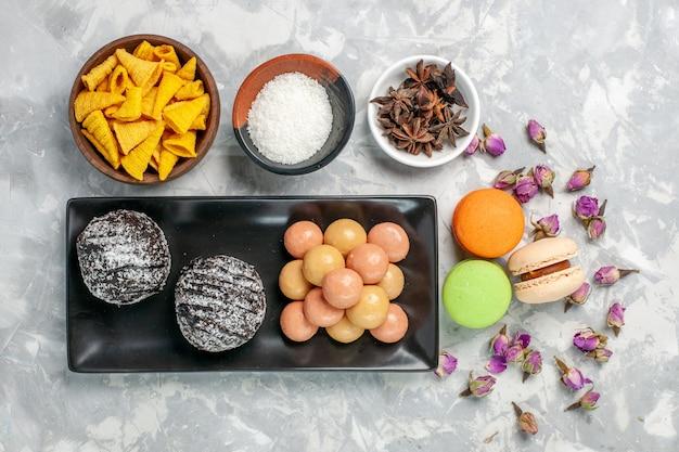 Vista superior deliciosos bolos de chocolate com biscoitos e macarons em uma superfície branca clara.