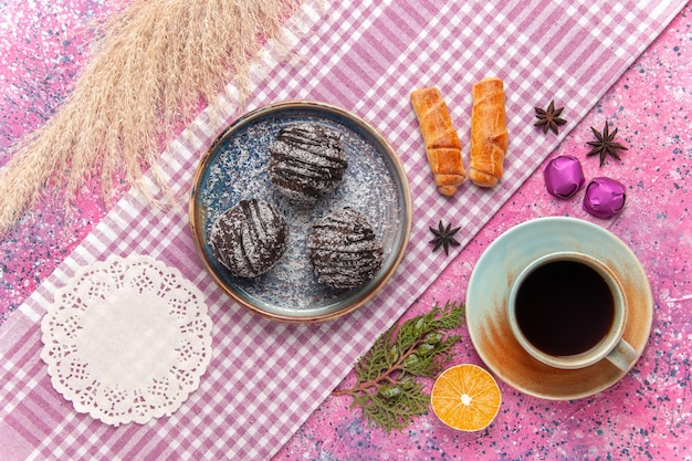 Vista superior deliciosos bolos de chocolate com uma xícara de chá rosa